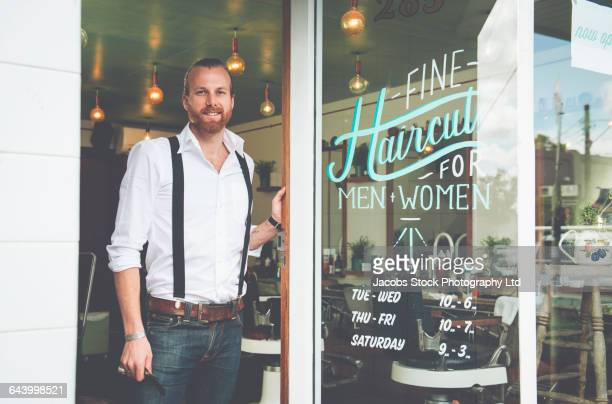 Caucasian stylist standing in barber shop doorway