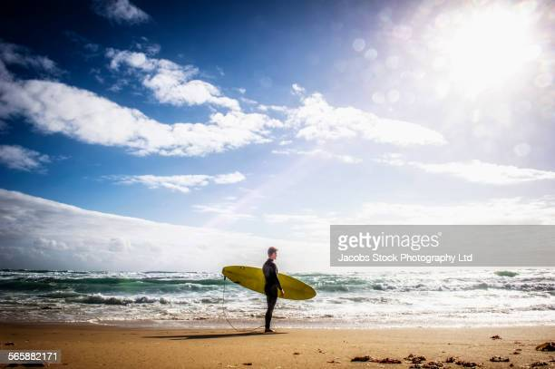 Caucasian surfer carrying surfboard on beach