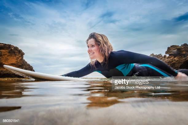 Caucasian surfer floating on surfboard in ocean