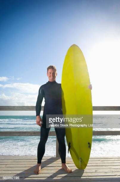Caucasian surfer holding surfboard on beach boardwalk
