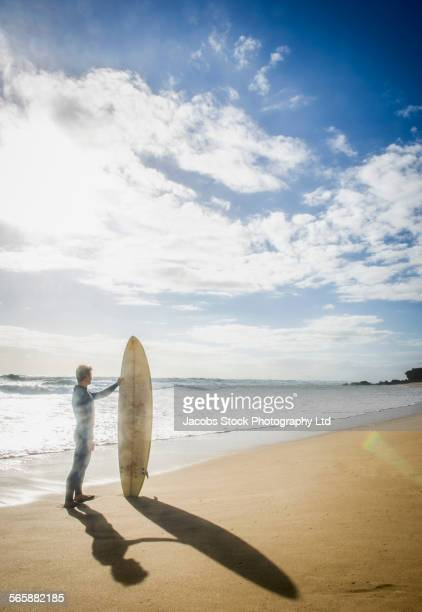 Caucasian surfer standing with surfboard on beach