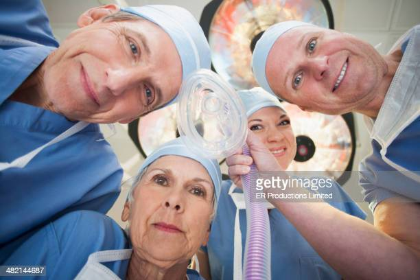 Caucasian surgeons holding oxygen mask in operating room