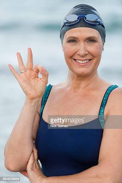 Caucasian swimmer making OK sign