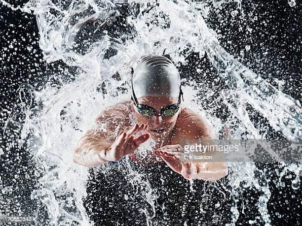 Caucasian swimmer splashing in water