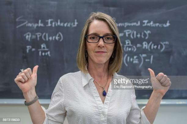Caucasian teacher cheering at chalkboard