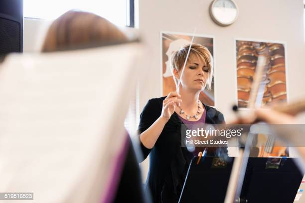 Caucasian teacher conducting music class