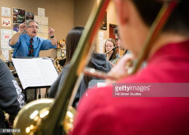 Caucasian teacher conducting students in music class