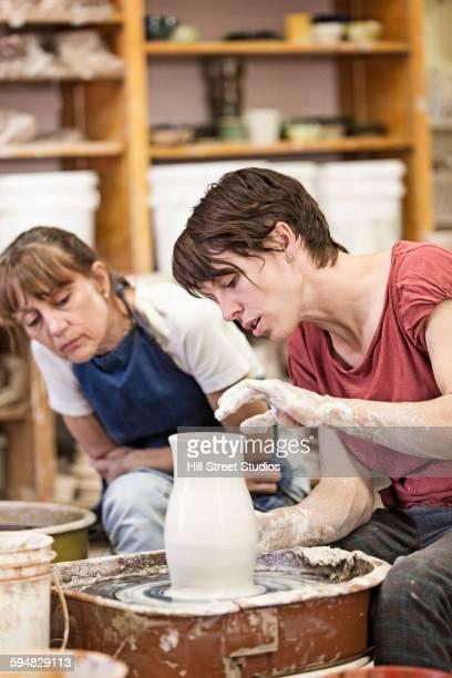 Caucasian teacher demonstrating pottery wheel for student