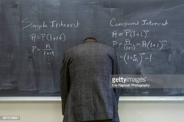 caucasian teacher frustrated at chalkboard - interest rate stock pictures, royalty-free photos & images