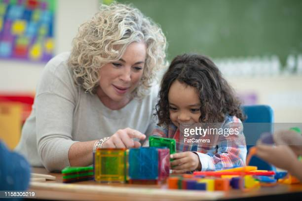 caucasian teacher plays magnetic blocks with her ethnic student - preschool student stock pictures, royalty-free photos & images