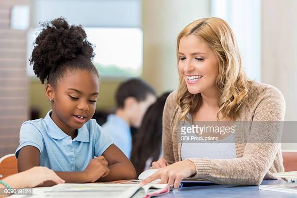 Caucasian Teacher reads with African American schoolgirl in library