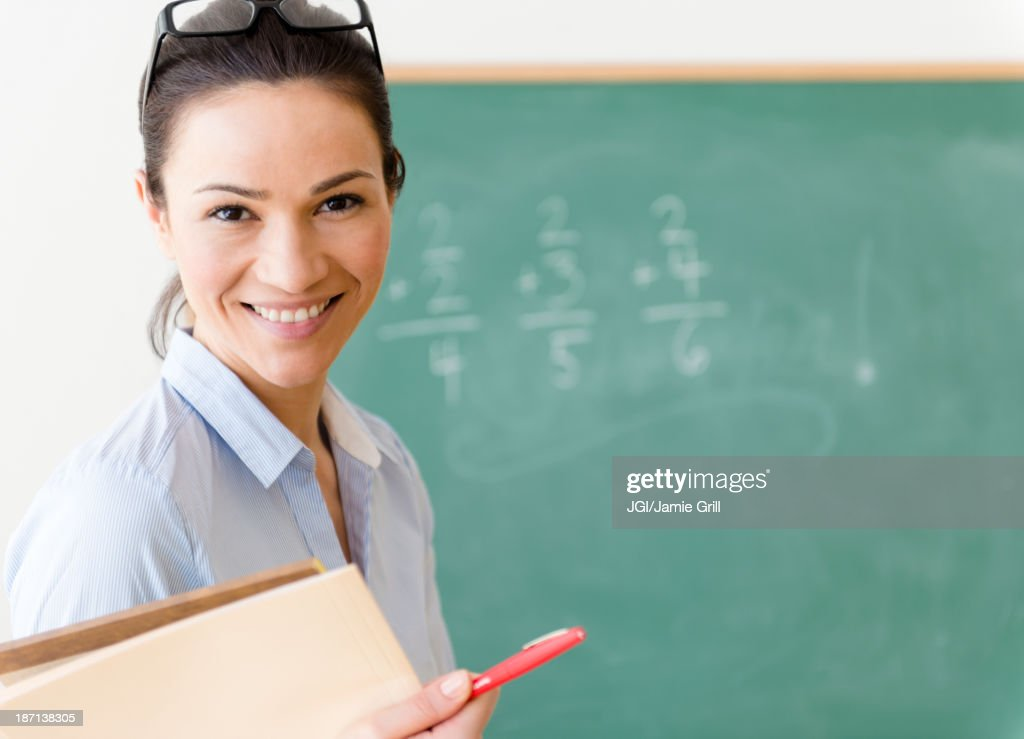 Caucasian teacher smiling in classroom : Stock Photo