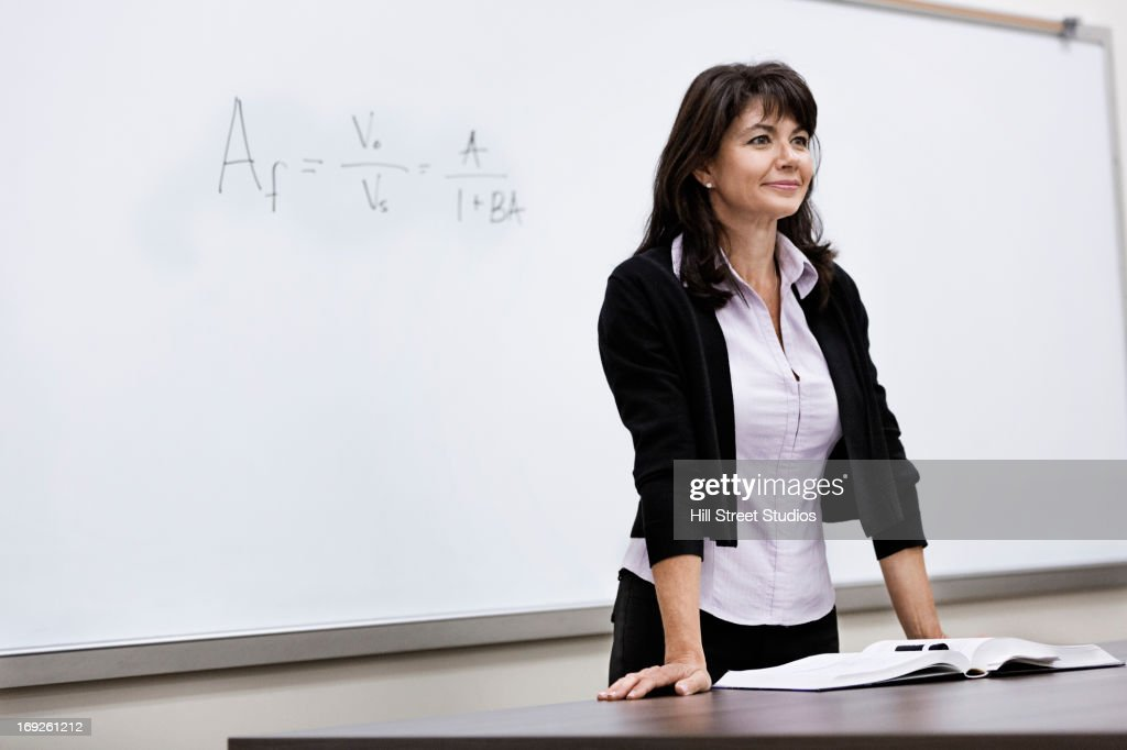 Caucasian teacher standing at whiteboard : Stock Photo