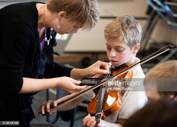 Caucasian teacher tuning students instrument in music class