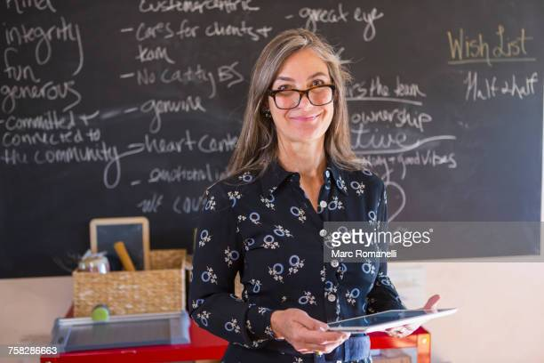 caucasian teacher using digital tablet in classroom - teacher stock pictures, royalty-free photos & images