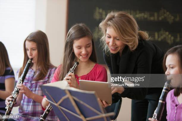 Caucasian teacher with digital tablet helping students in music class