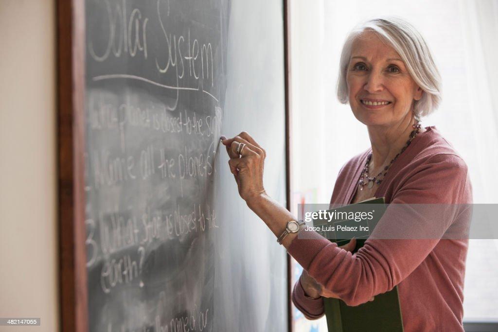 Caucasian teacher writing on chalkboard : Stock Photo