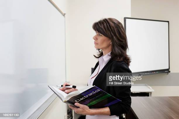 Caucasian teacher writing on whiteboard