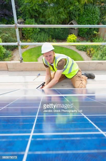 Caucasian technician caulking solar panels