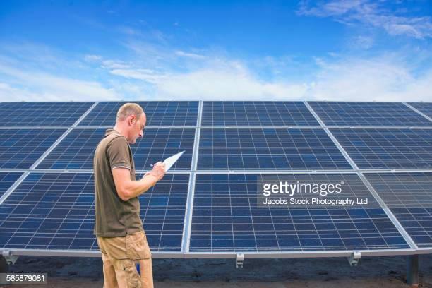 caucasian technician examining solar panels - spalding england stock photos and pictures