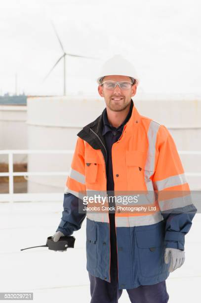 Caucasian technician holding walkie-talkie on fuel storage tank