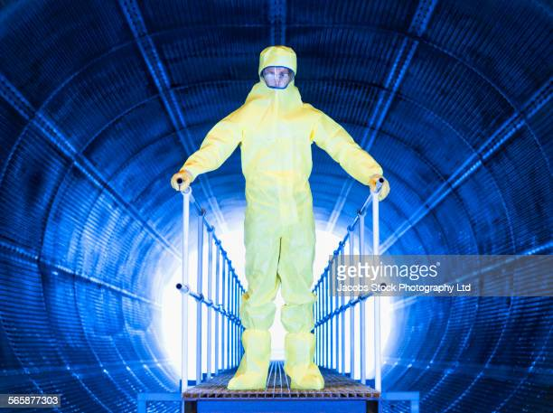 caucasian technician in protective suit on tunnel walkway - hazmat suit stock pictures, royalty-free photos & images