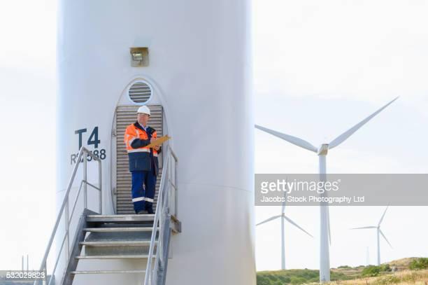 Caucasian technician reading paperwork near wind turbine