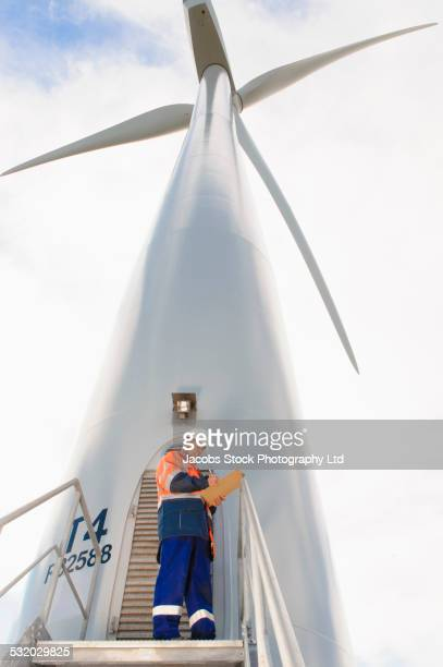 Caucasian technician reading paperwork under wind turbine