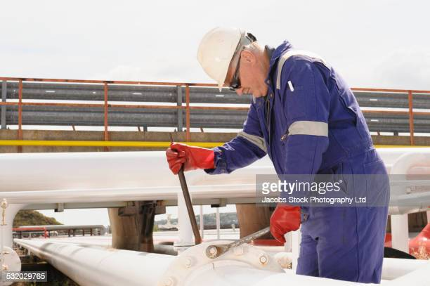 caucasian technician tightening bolts on pipe - tighten stock pictures, royalty-free photos & images