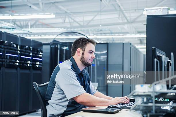 Caucasian technician using computer in server room