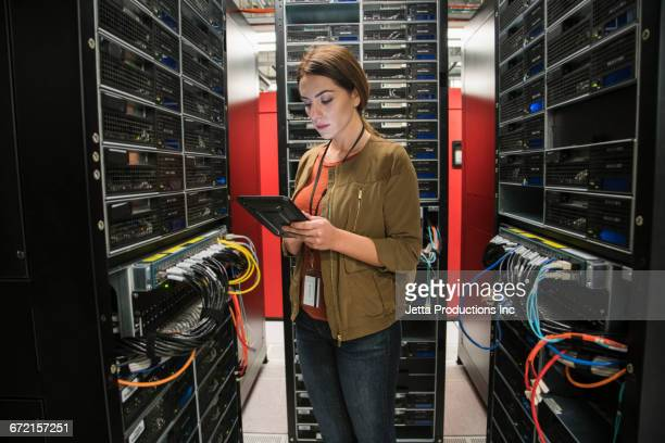 caucasian technician using digital tablet in computer server room - jetta productions stock pictures, royalty-free photos & images