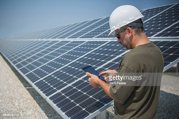 Caucasian technician using digital tablet near solar panels