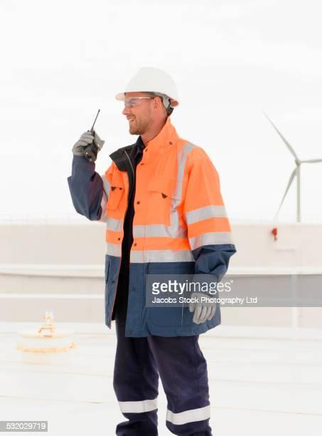Caucasian technician using walkie-talkie on fuel storage tank