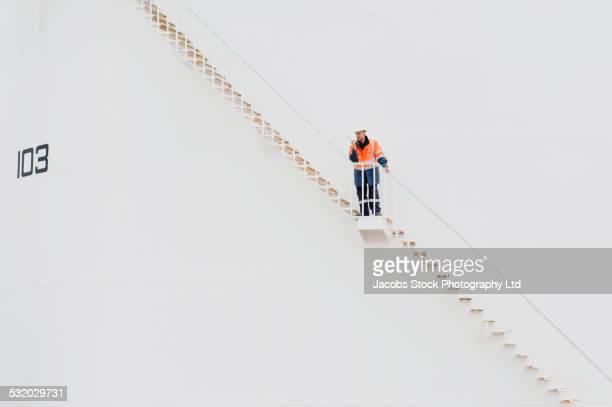 caucasian technician using walkie-talkie on fuel storage tank staircase - vorratstank stock-fotos und bilder