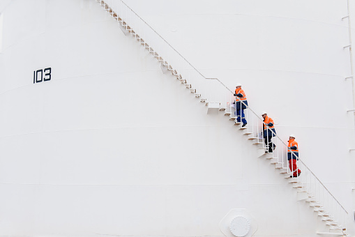 Caucasian technicians climbing fuel storage tank staircase - gettyimageskorea
