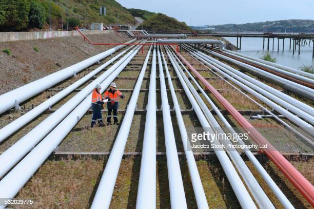 caucasian technicians examining pipes - marine engineering stock pictures, royalty-free photos & images