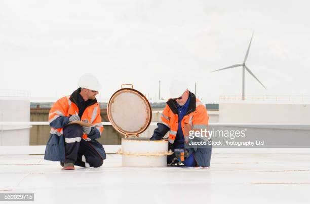 Caucasian technicians performing gas meter test on fuel storage tank