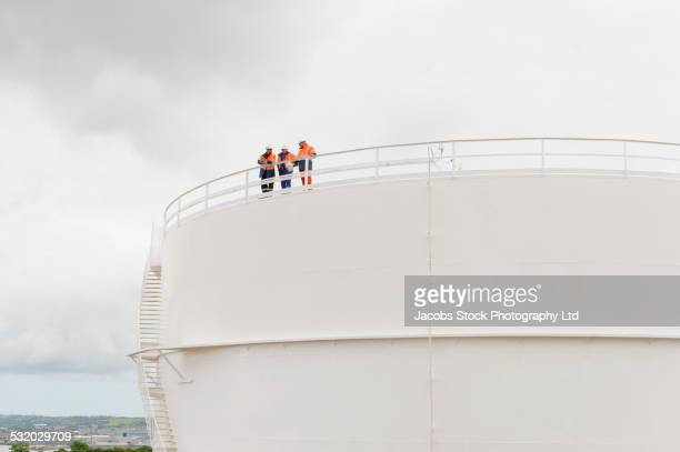 caucasian technicians standing on fuel storage tank - marine engineering stock pictures, royalty-free photos & images