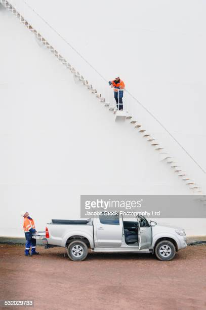 Caucasian technicians talking at fuel storage tank staircase