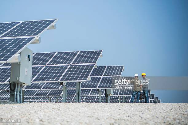 Caucasian technicians talking near solar panels