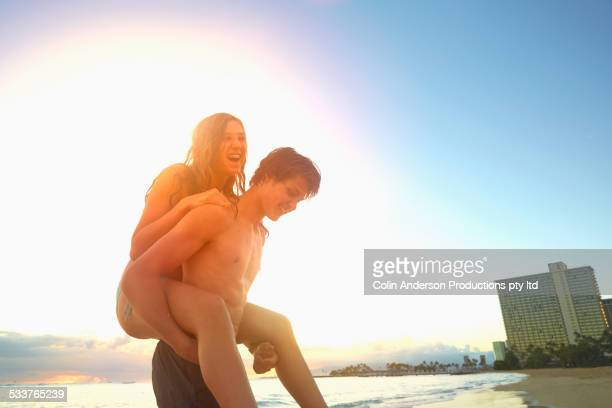 Caucasian teenage boy carrying sister on beach