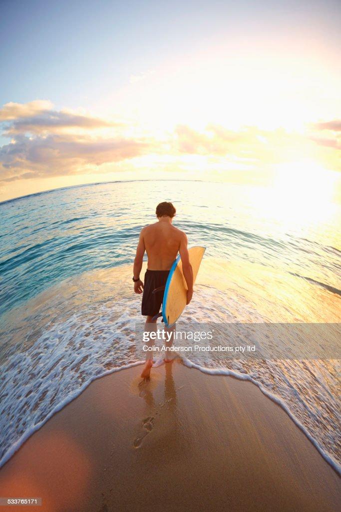 Caucasian teenage boy carrying surfboard on beach : Foto stock