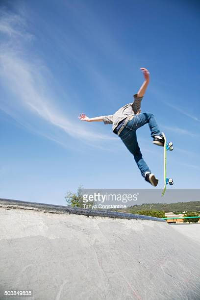 Caucasian teenage boy doing tricks in skate park