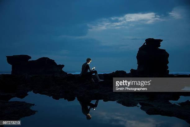 Caucasian teenage boy exploring rocky tidal pools at night, Canggu, Bali, Indonesia