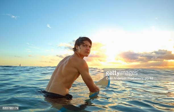 Caucasian teenage boy floating on surfboard in ocean
