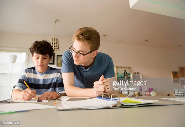 Caucasian teenage boy helping brother with homework