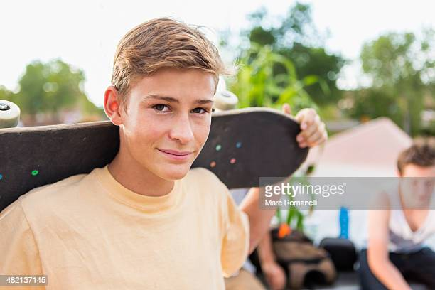 caucasian teenage boy holding skateboard - incidental people stock pictures, royalty-free photos & images