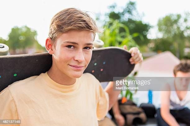 Caucasian teenage boy holding skateboard