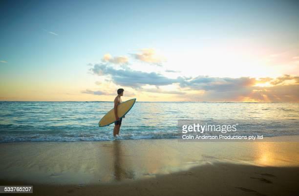Caucasian teenage boy holding surfboard on beach