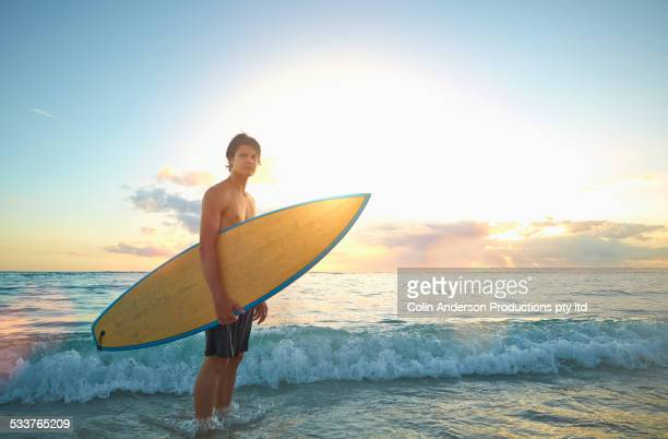Caucasian teenage boy holding surfboard on beach